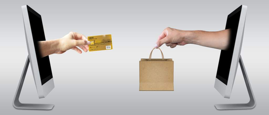 Two screens facing each other, each with a hand coming out of the screen. On the left, the hand is holding a credit card, on the right the hand is holding a paper shopping bag.