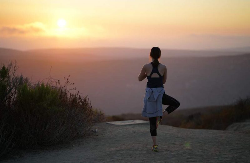 Woman with back to camera, standing doing yoga and looking at the sunset