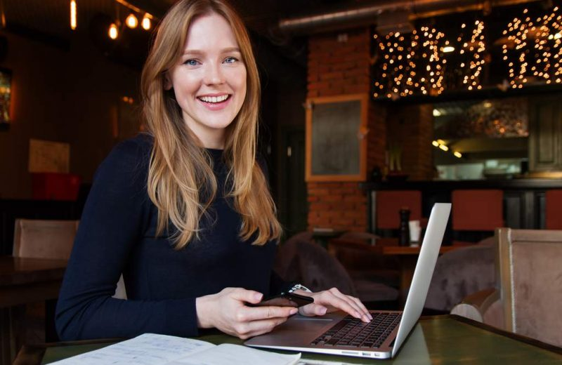 Business woman with long hair, a laptop and a phone in one hand, looking at viewer.