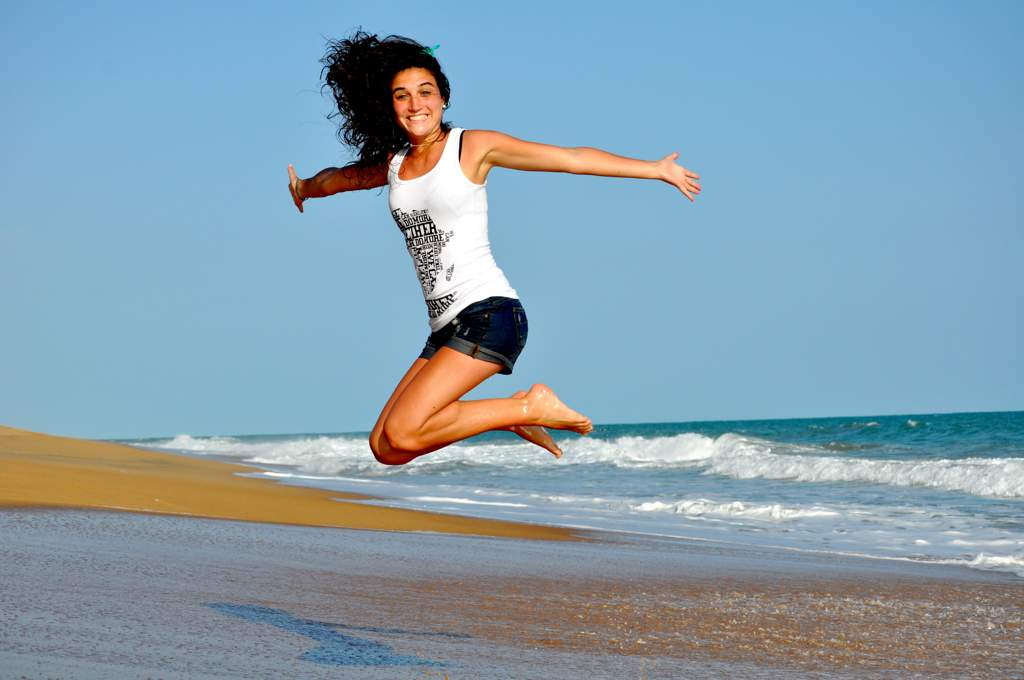Woman in white tee shirt and black shorts jumping into the air on a sandy beach with sea in the background.