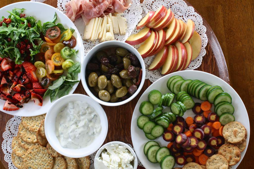 Bowls of summer food including salad, olives, apple slices and sandwiches