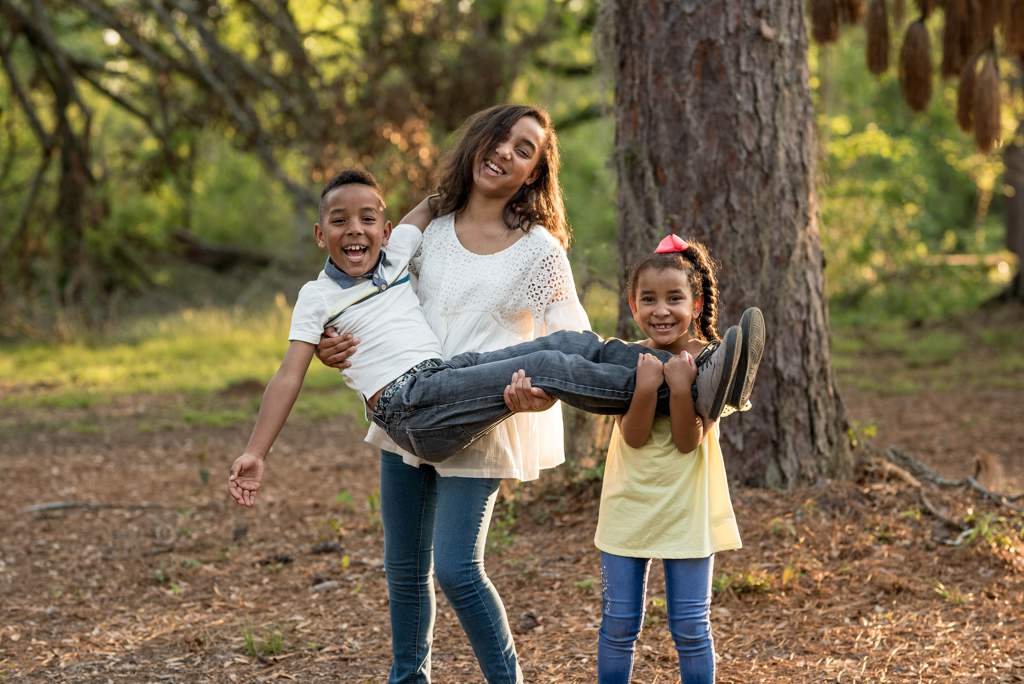 Woman in woodland, carrying a boy, a young girl is also carrying the boy, all are smiling and laughing.