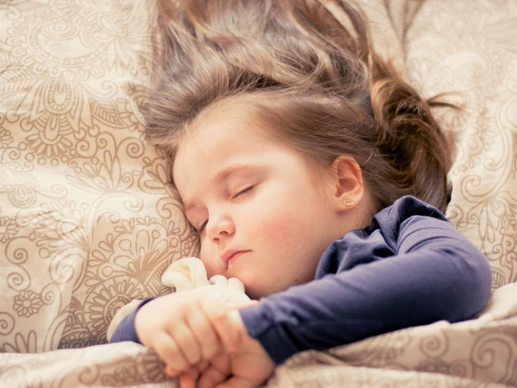Little girl sleeping on a patterned background, cuddling a soft toy.