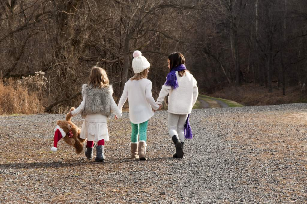 Three little girls walking away from us down a road, holding hands. The girl on the left is carrying a teddy bear which is wearing a Santa hat.