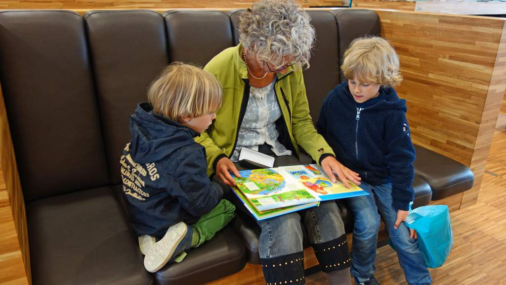 Granny is sitting reading a picture book with two boys under 10.