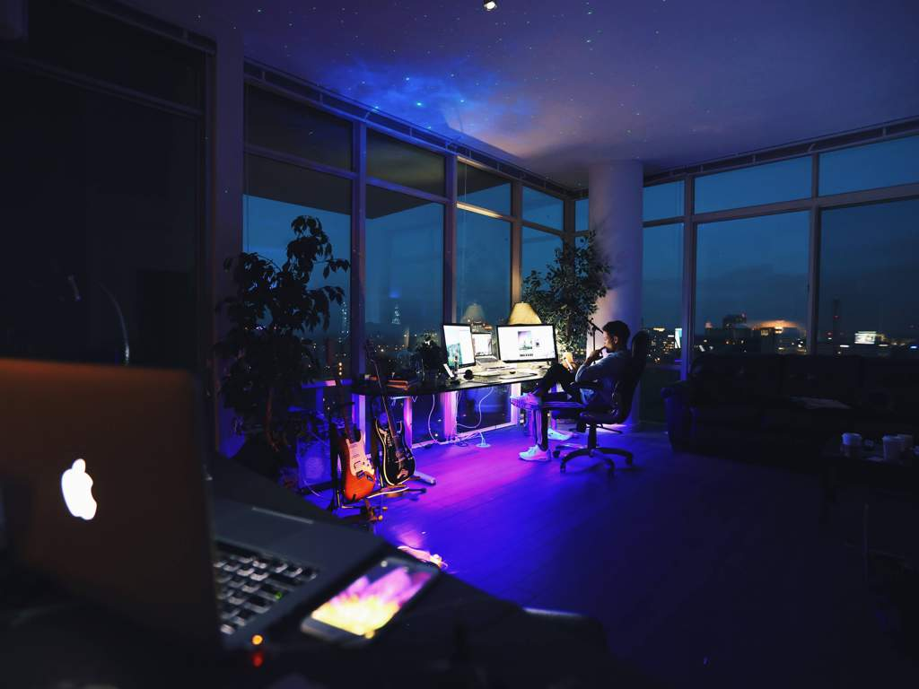 Hi Tech home office in corner of room with floor to ceiling windows looking out over a city at night. Lighting is purple, man sits at a bank of monitors, and there are electric guitars next to the desk.