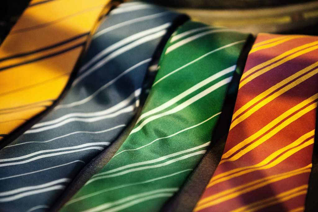 Display of four colored ties with diagonal stripes in the colors of the houses of Hogwarts from the Harry Potter series..