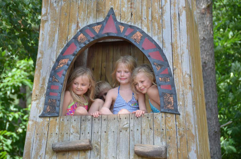 Three young girls looking down from tree house. There's a little boy just visible behind them.