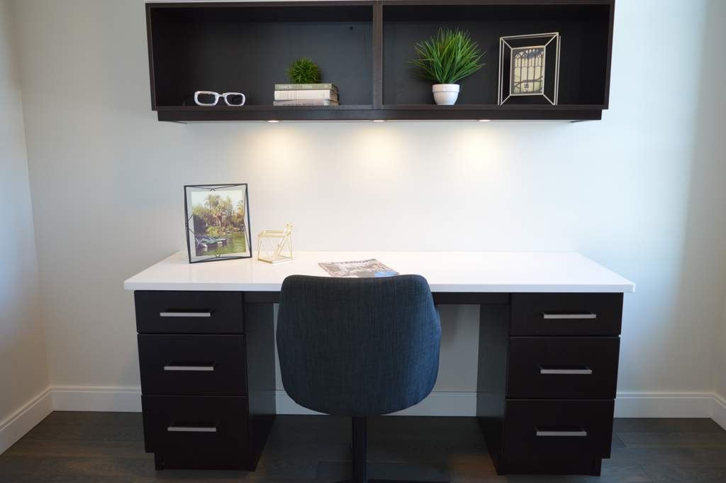 Dark wood desk with white top and dark wooden shelves above against a white wall. There is a chair at the desk. The overall effect is uncluttered and minimalist.