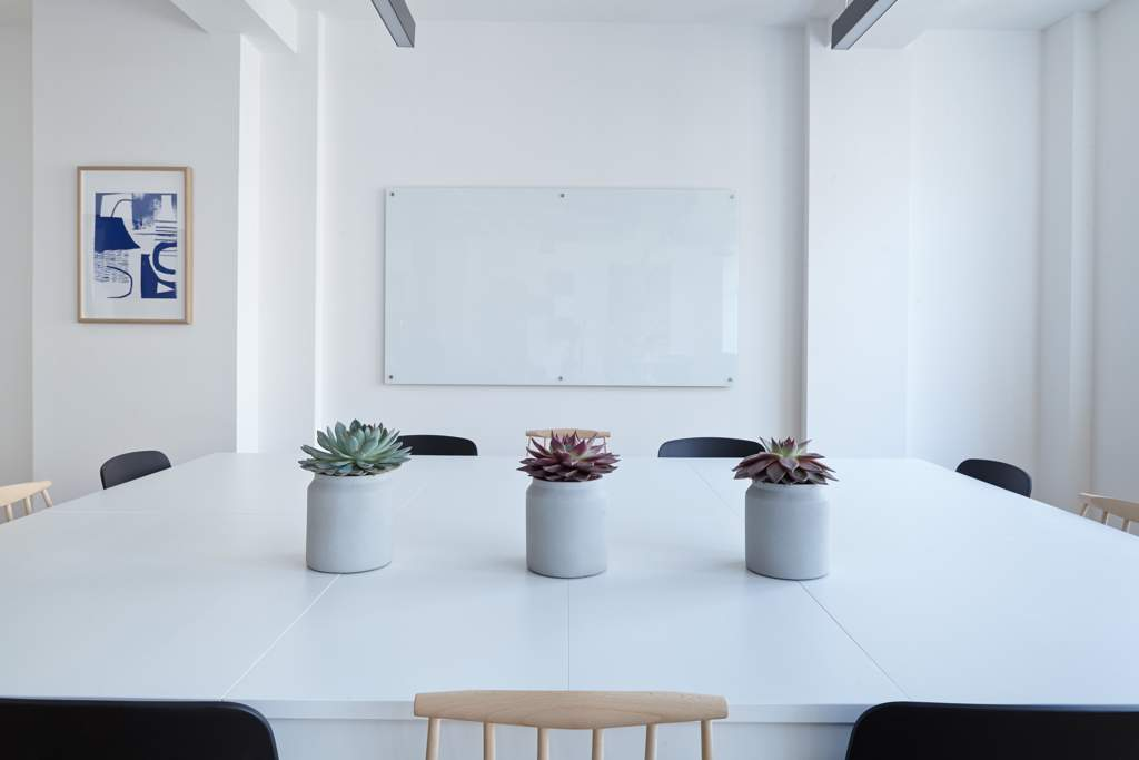 Large white table with three plants and chairs around it faces a whiteboard in a white room.