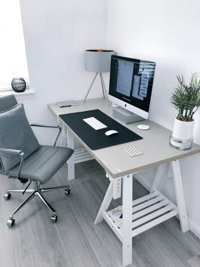Grey minimalist home office with a grey-topped trestle table with computer screen, and a grey office chair on a grey wooden floor.