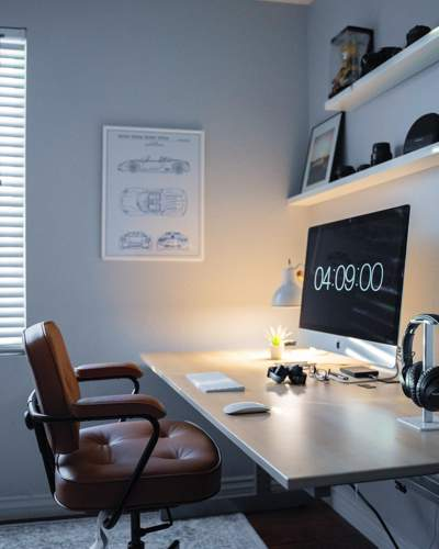 Minimalist home office in a corner of a soft grey room. There is a red leather swivel chair at the desk.