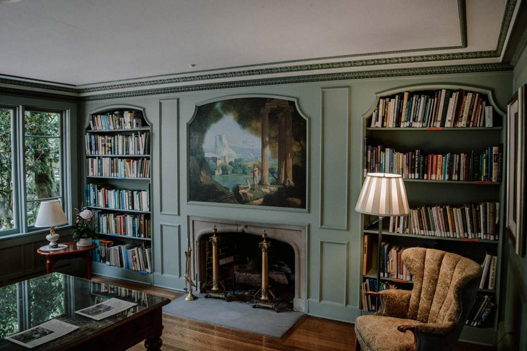 Old fashioned office with green built-in bookcases filled with books. There is a chair in the corner and a standard lamp. Between the bookcases is a fireplace with a painting above.There is also a desk.
