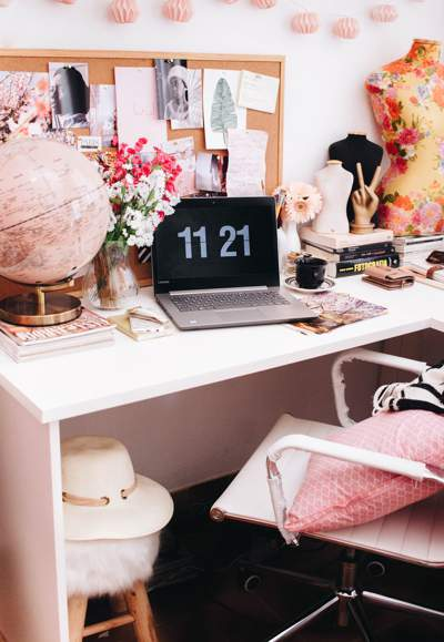 Home office with pink and pastel colors - a laptop sits on the desk next to a pink globe and dress making patterns - there is a noticeboard on the wall with things pinned to it, a pink cushion on the chair and flowers on the desk.