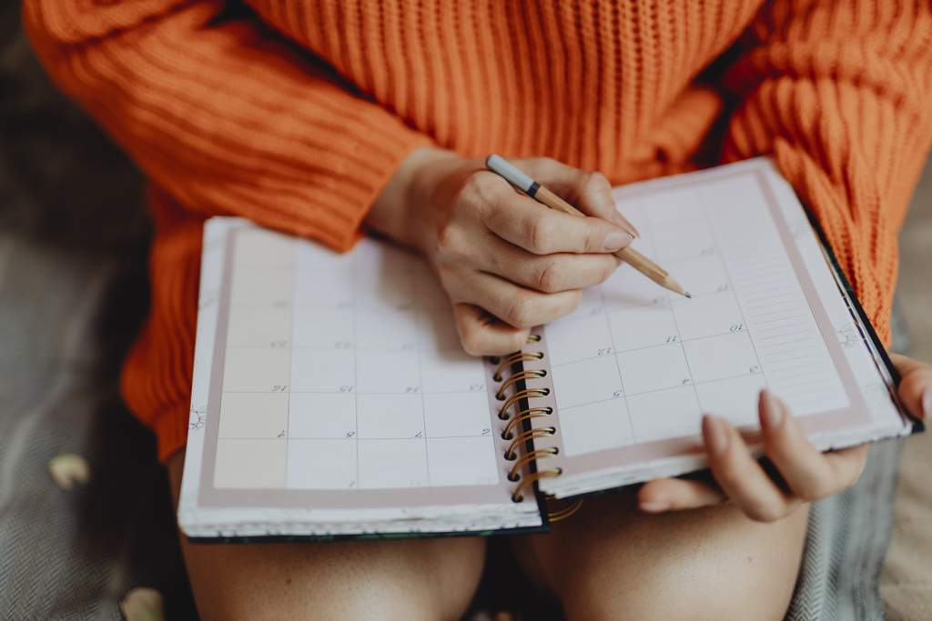 Woman wearing orange top is writing in her calendar or diary with a pencil.