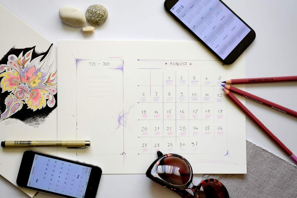 Desktop with a calendar and to-do list for August. Also on the desk is a drawing, three pencils, two mobile phones, and pair of sunglasses and a pen.
