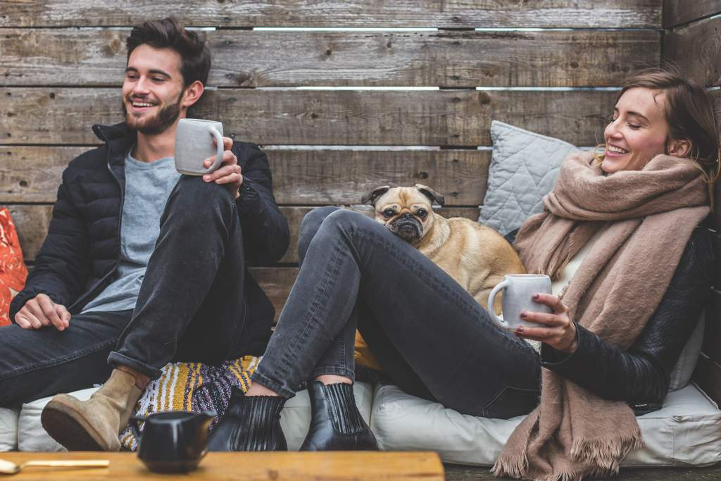 Young man and woman sitting on sofa drinking from large grey mugs. The woman has a large scarf and is holding a small pug-type dog. There is a rough wooden background.