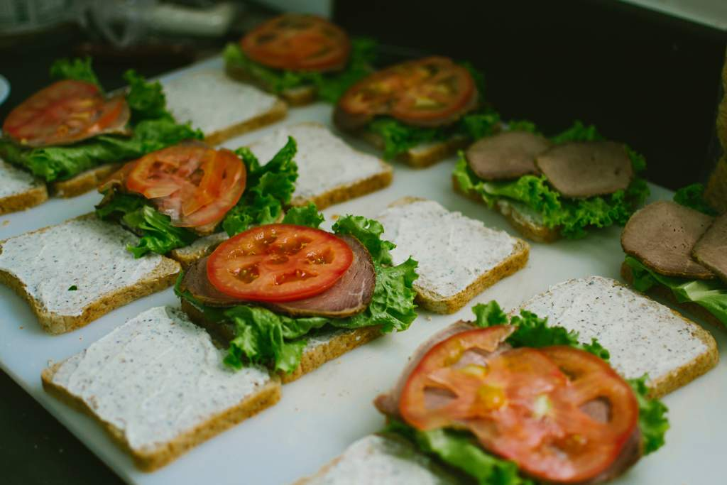 Sandwiches being prepared - they contain lettuce tomato and slices of beef.