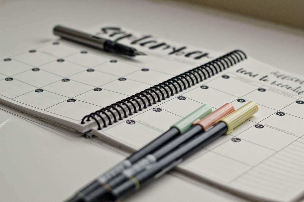 A notebook diary and calendar sitting on a white desk with four pens.