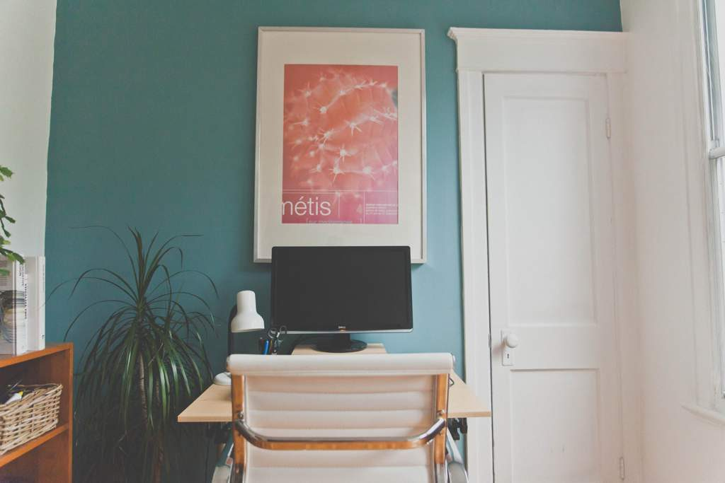 A small table and white chair facing a red picture on a blue/green wall with a white door. There is a monitor and lamp on the desk.