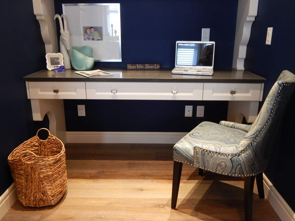 White table with laptop and a shelf above it runs the full width of this tiny room. Walls are painted dark blue and there's an upholstered chair next to the desk.