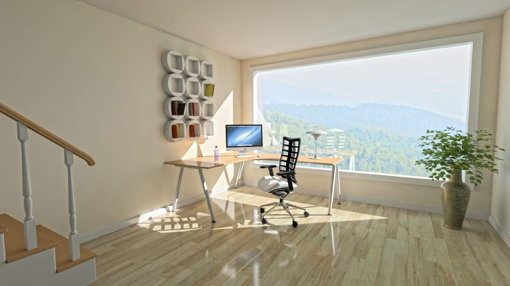 Corner desk with monitor and very modern looking chair on a polished wooden floor. The desk stands in front of an enormous window looking out over a spectacular view of a forest.