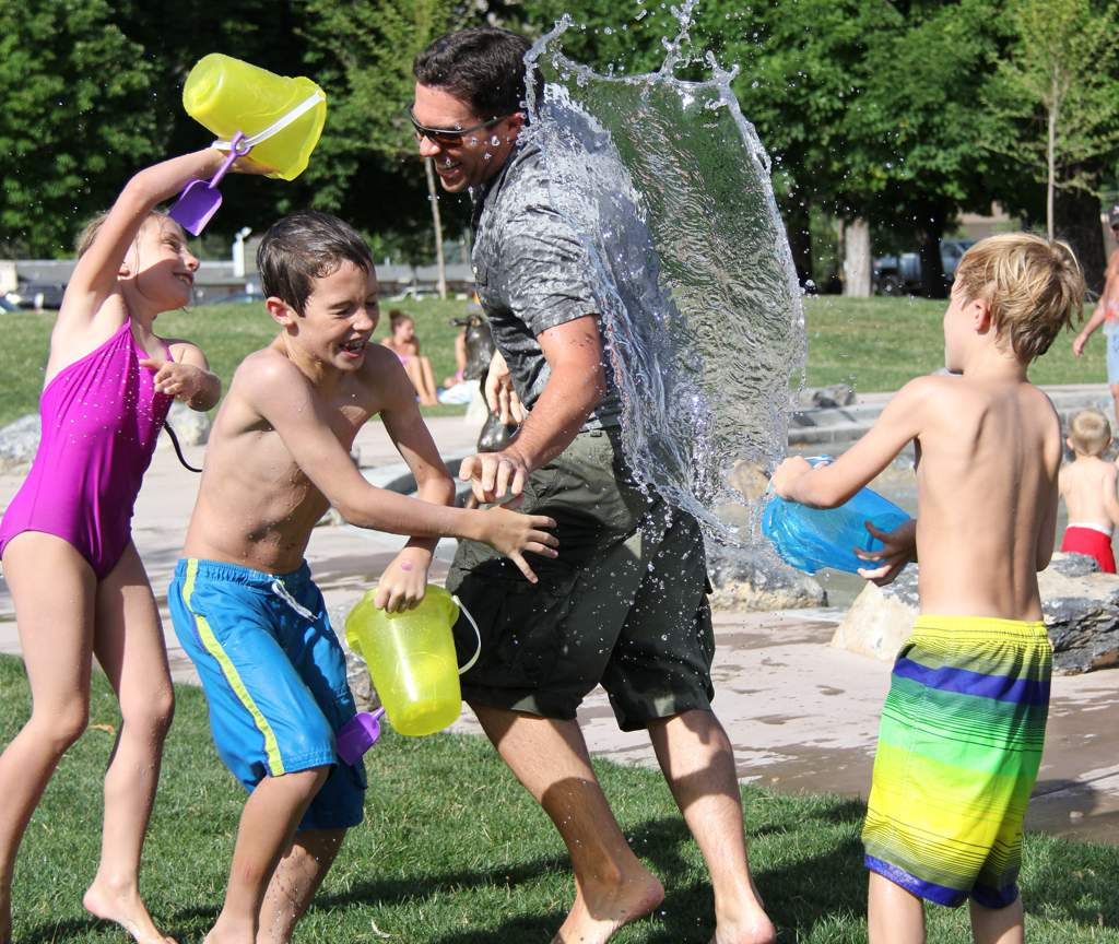 A water fight in the park: Two boys and a girl are throwing water over an adult man on a sunny day - everyone is laughing.