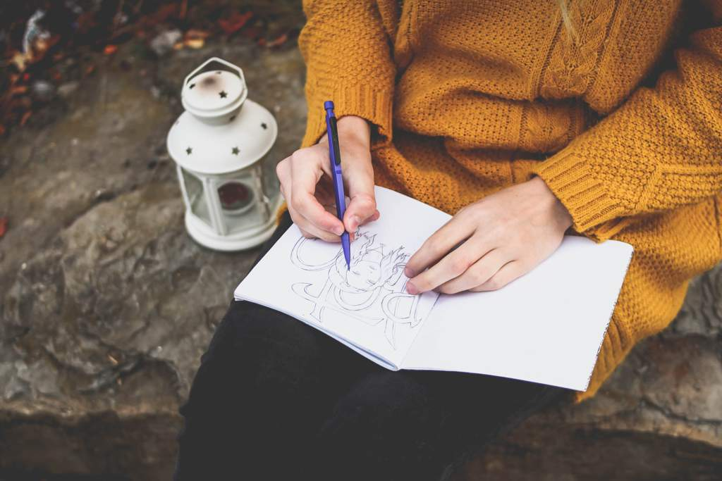 Woman in mustard-colored top sitting drawing in notebook. There is a white lantern beside her.