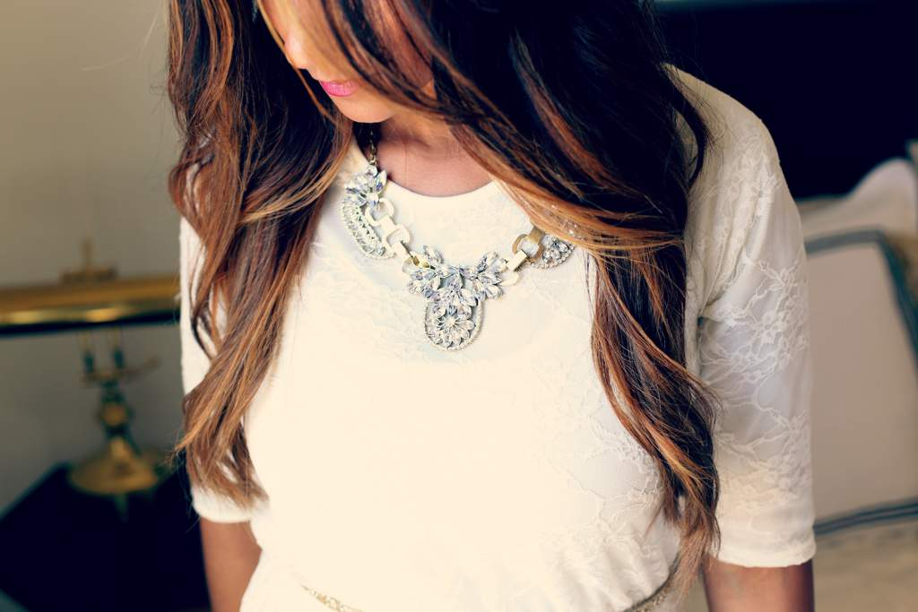 Woman wearing a cream colored top and a chunky metal and white stone necklace.