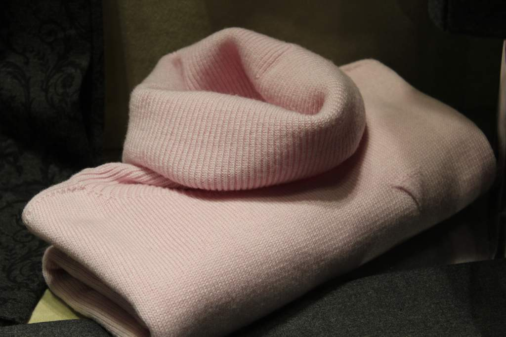 A pale pink roll-neck fluffy jumper.