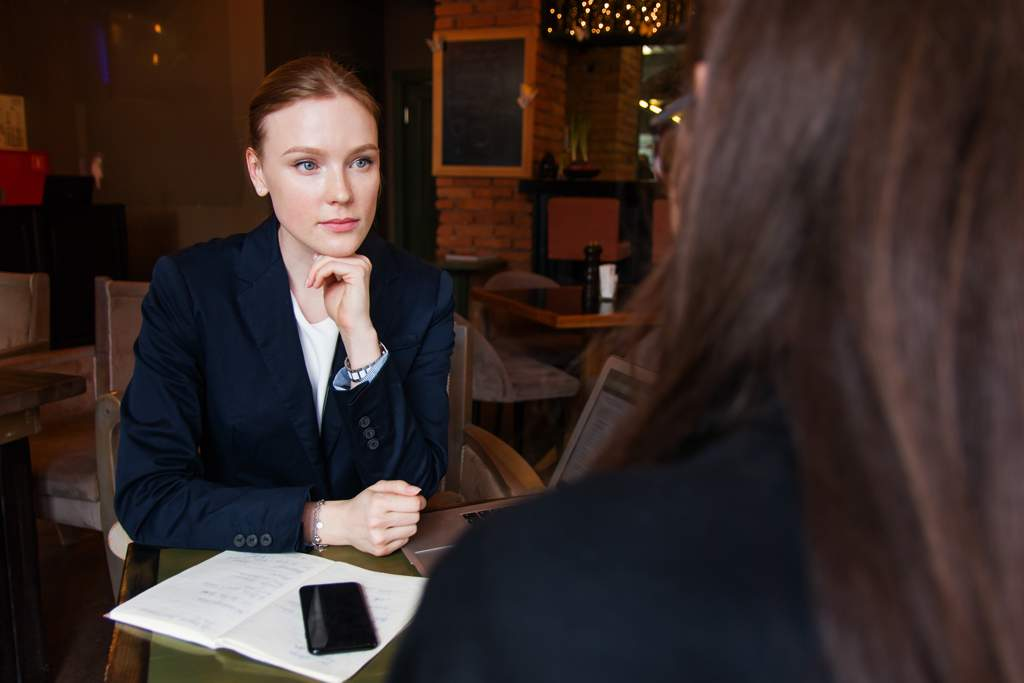 Two business women meeting in a coffee shop. We're behind one, looking over her shoulder. The other woman is facing the camera, and is wearing a dark blue jacket over a white blouse. There is a laptop, notebook and phone on the table.