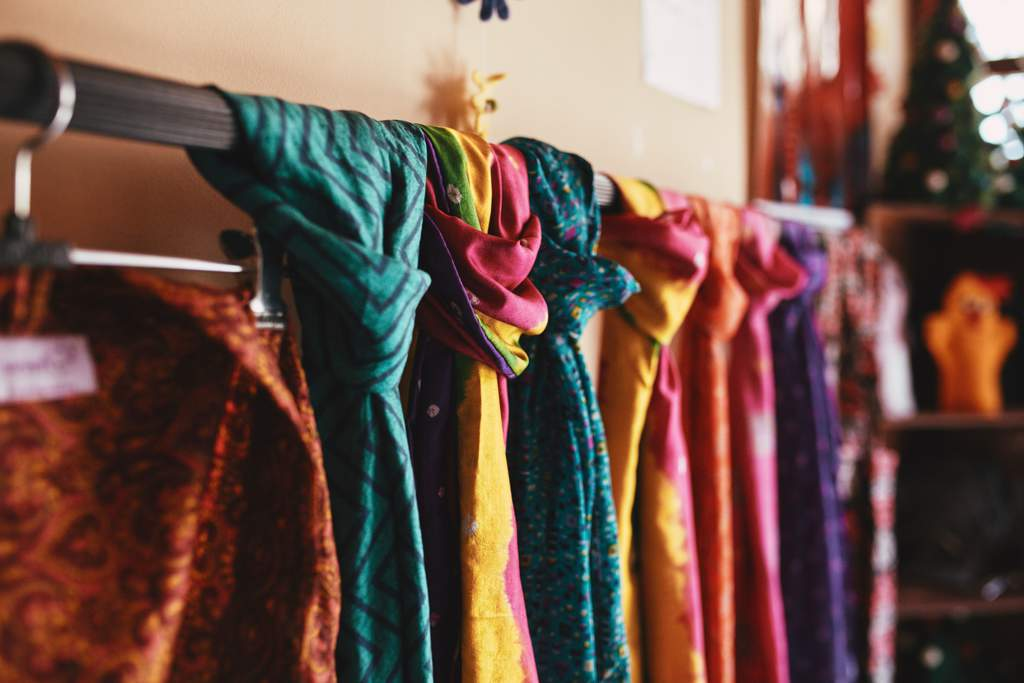 A row of brightly colored silk scarves hanging on a rail in a shop.