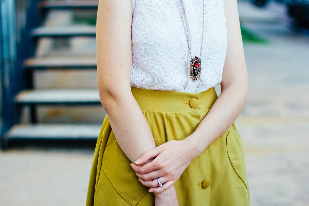 Woman wearing mustard skirt and a white top with a large pendant necklace.
