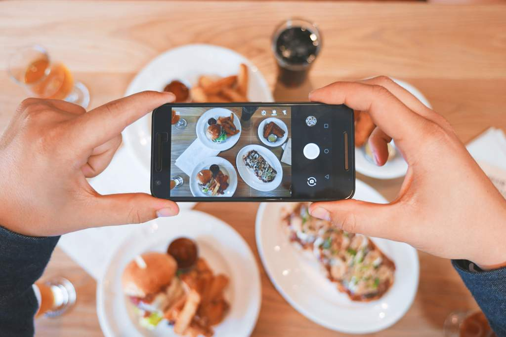Hands holding a cellphone and taking a photo of 4 plates of food.