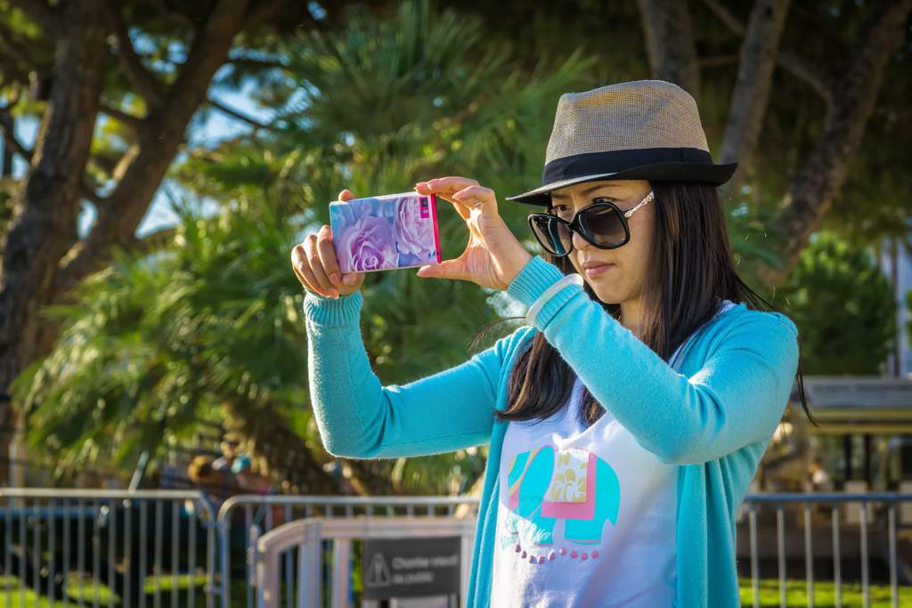 Dark haired woman wearing a hat, sunglasses and a bright blue top taking a photo on a cellphone.