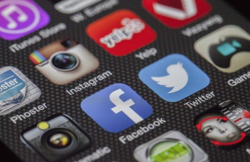 Close-up of a smartphone screen showing app icons. In focus are icons for social networks Facebook and Twitter.