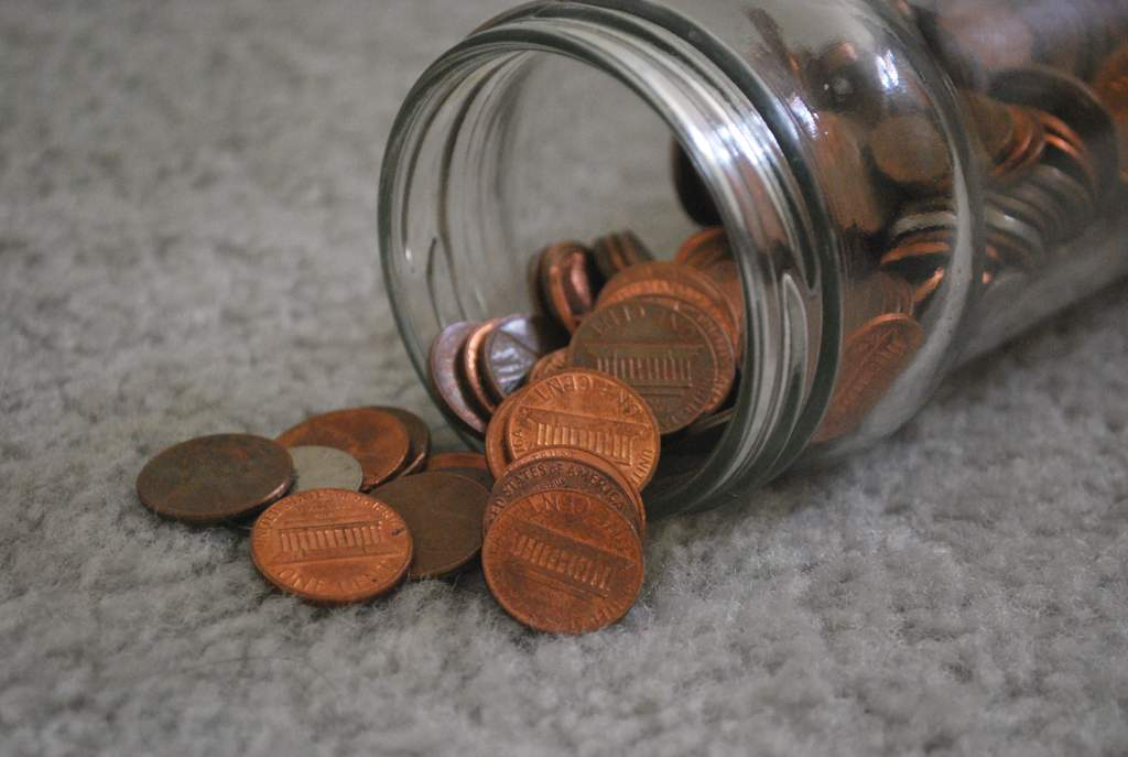 Glass jar lying on its side on a gray carpet with copper colored one cent coins spilling out.