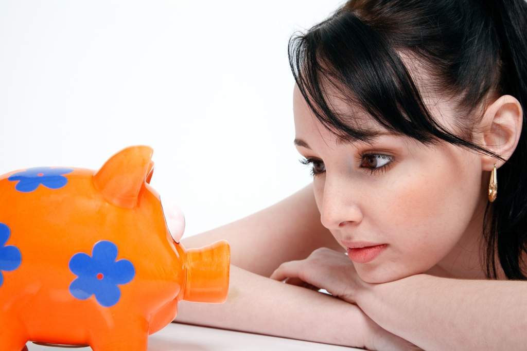 Young dark-haired woman looking at a bright orange piggy bank with blue flowers on it.