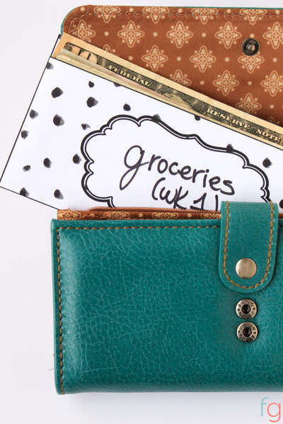Printed patterned envelope labelled groceries (wk1) containing cash, underneath a teal colored wallet.
