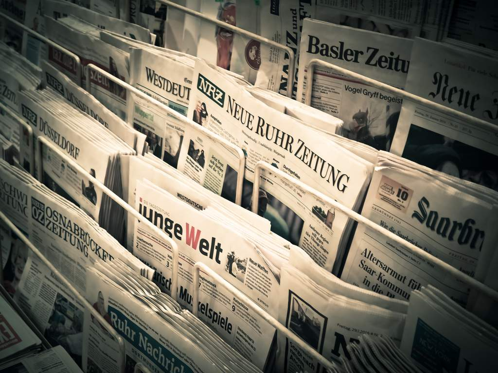 A rack of newspapers showing headlines.