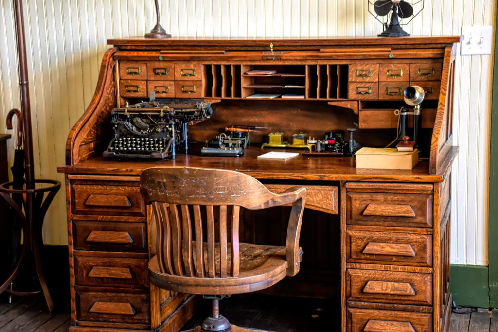 Old fashioned wooden desk and chair with an old typewriter and telephone on the desk.