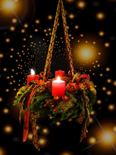 Hanging Christmas decoration with green foliage and red candles seen against a black background with lights.