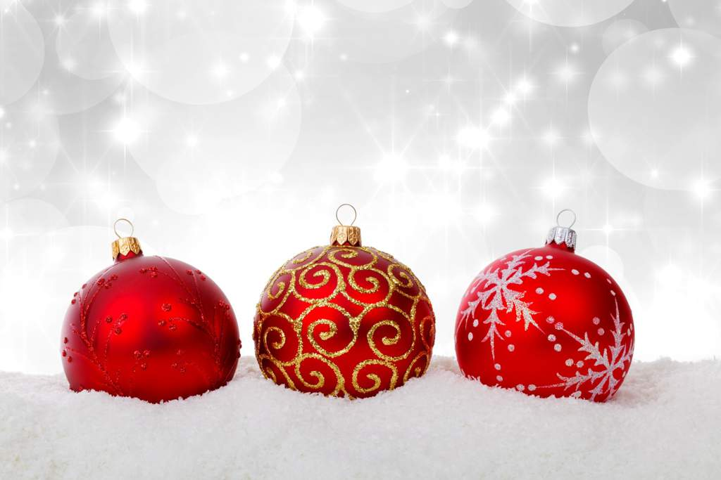 Three red baubles in the snow. The left hand one is all red, the middle one has a gold-glitter design and the right hand once has a snowflake design in white frosting.
