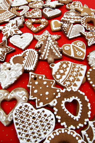 Selection of Christmas cookies with white icing on a red background.