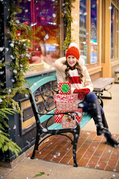Woman wearing red hat and gloves sitting on a bench outside a shop with a pile of gift-wrapped presents on a snowy day.