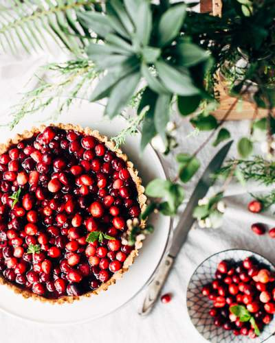 Cranberry pie served on a white plate on a white tablecloth with green foliage and a small bowl of cranberries.