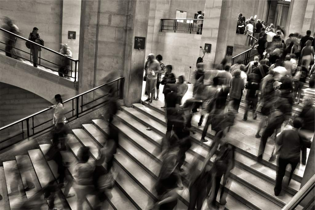 Crowd of people walking up and down large flights of stone stairs. Picture is in black and white and people are blurred as they are moving.