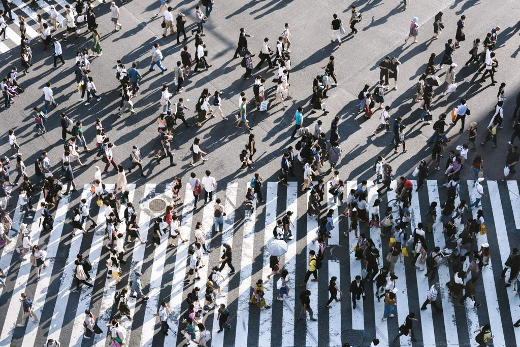 Aerial view of a large number of people crossing a road at a zebra crossing.