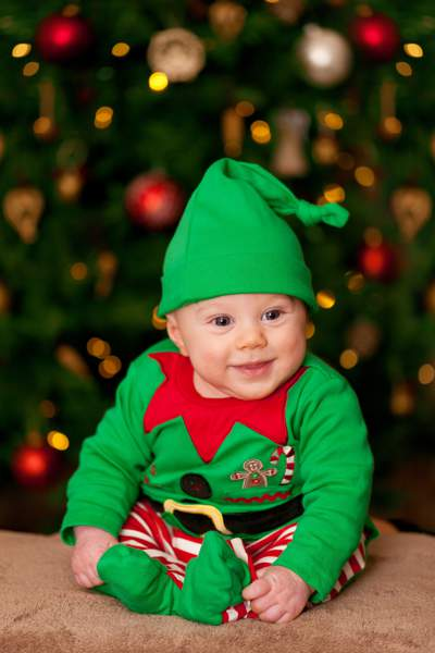 Baby dressed in a green and red Christmas Elf costume with a green pointy hat.