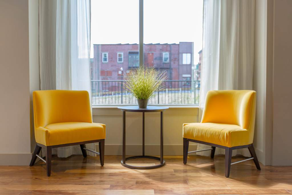 Two yellow chairs in front of a window. Between the chairs is a table with a plant on it. There are curtains at the window and a red building outside.